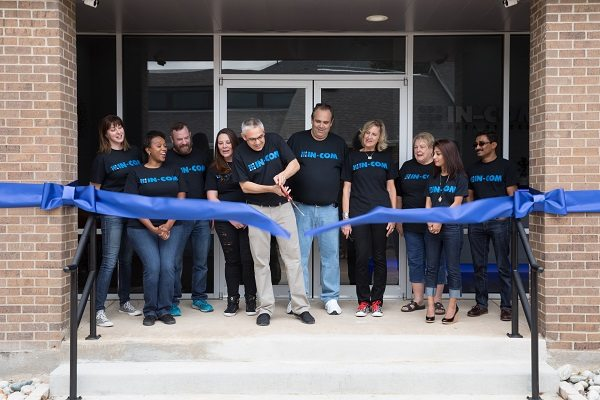Cutting the ribbon in front of the new IN-COM offices